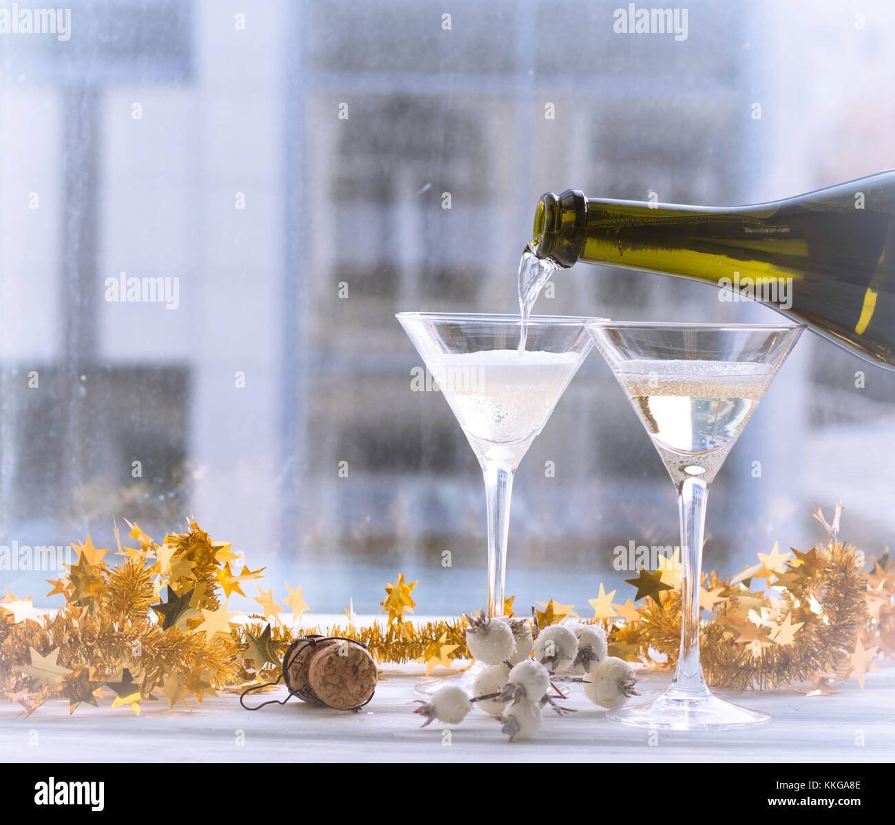 Champagne is being poured into a glass - Stock Image