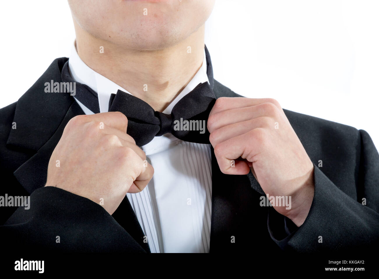 18 year old wearing a tuxedo adjusting his bowtie isolated on a white background - Stock Image
