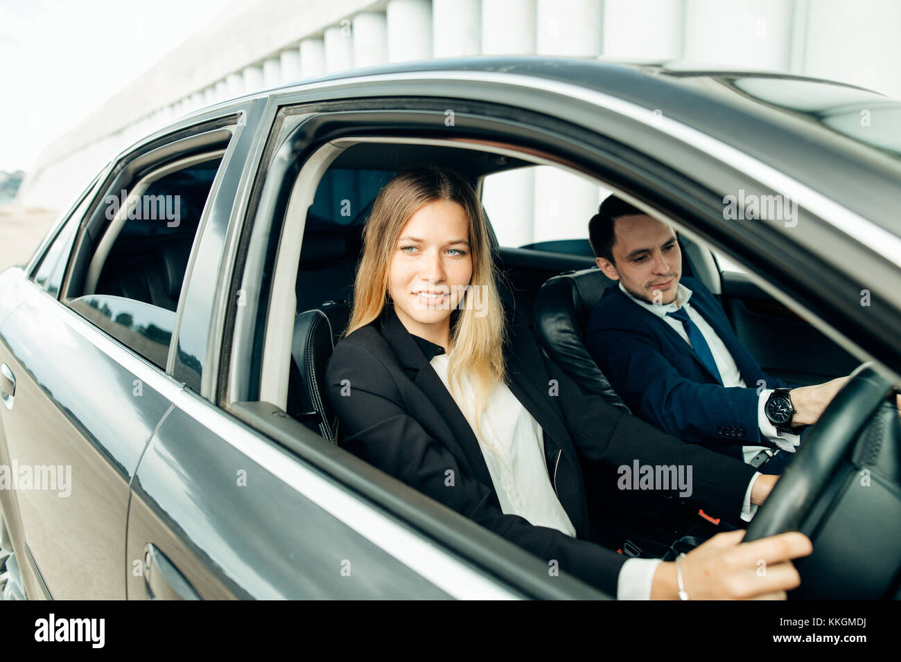Driving instructor and woman student in examination car. - Stock Image