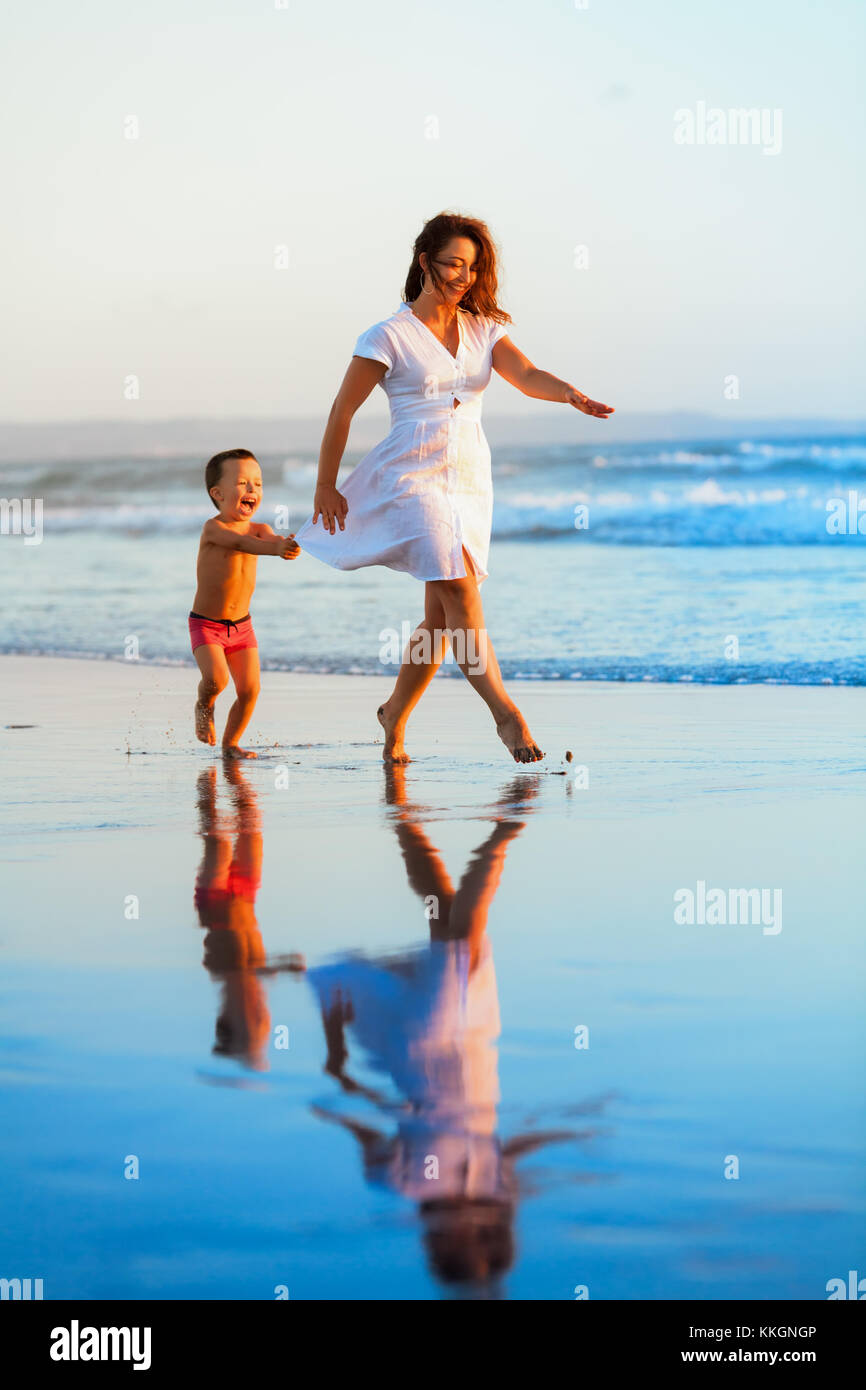 Happy family holiday - mother, baby son have fun together, barefoot child run by water pool along sunset sea surf - Stock Image