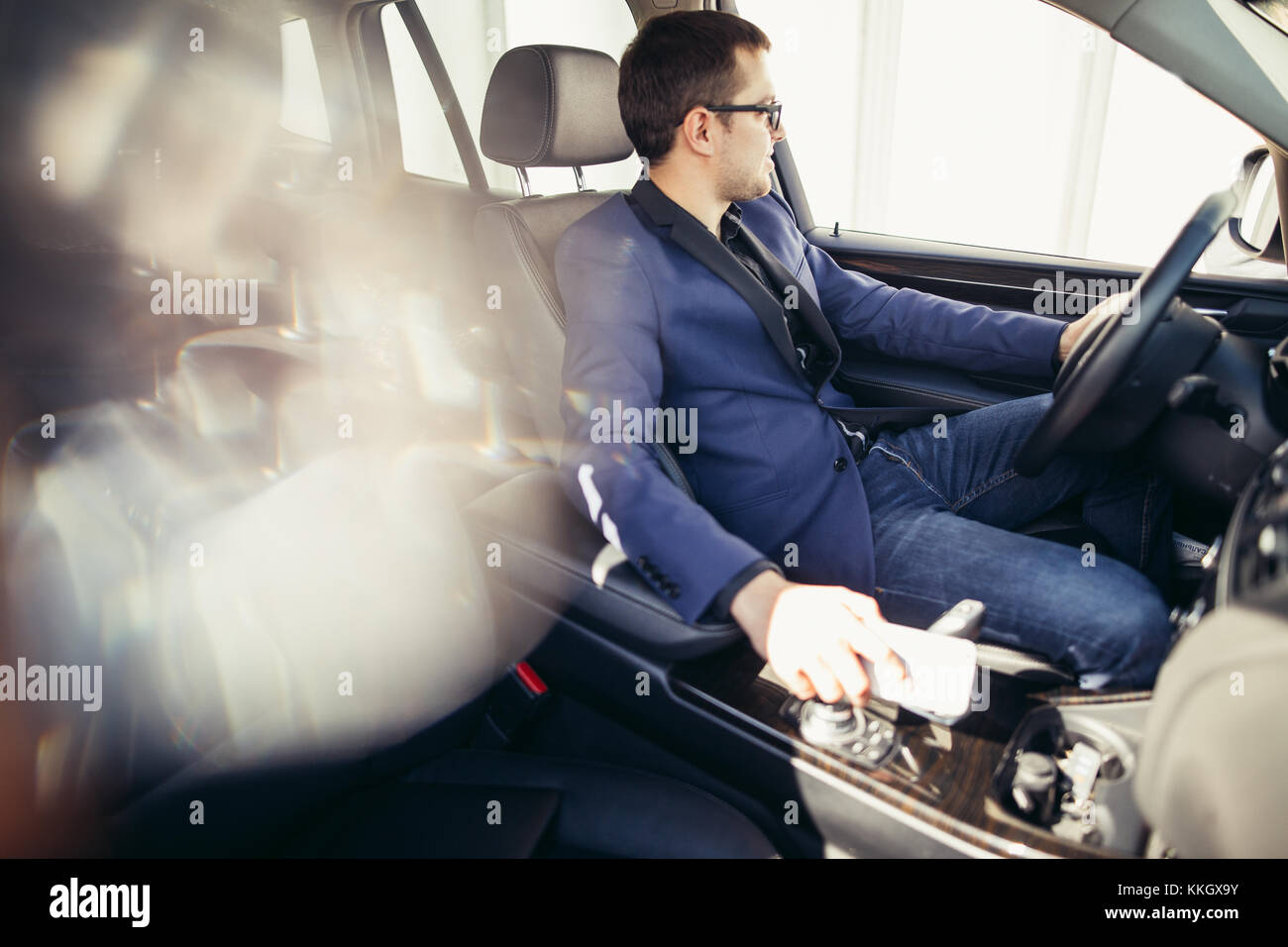 Portrait of an handsome smiling business man driving his car - Stock Image