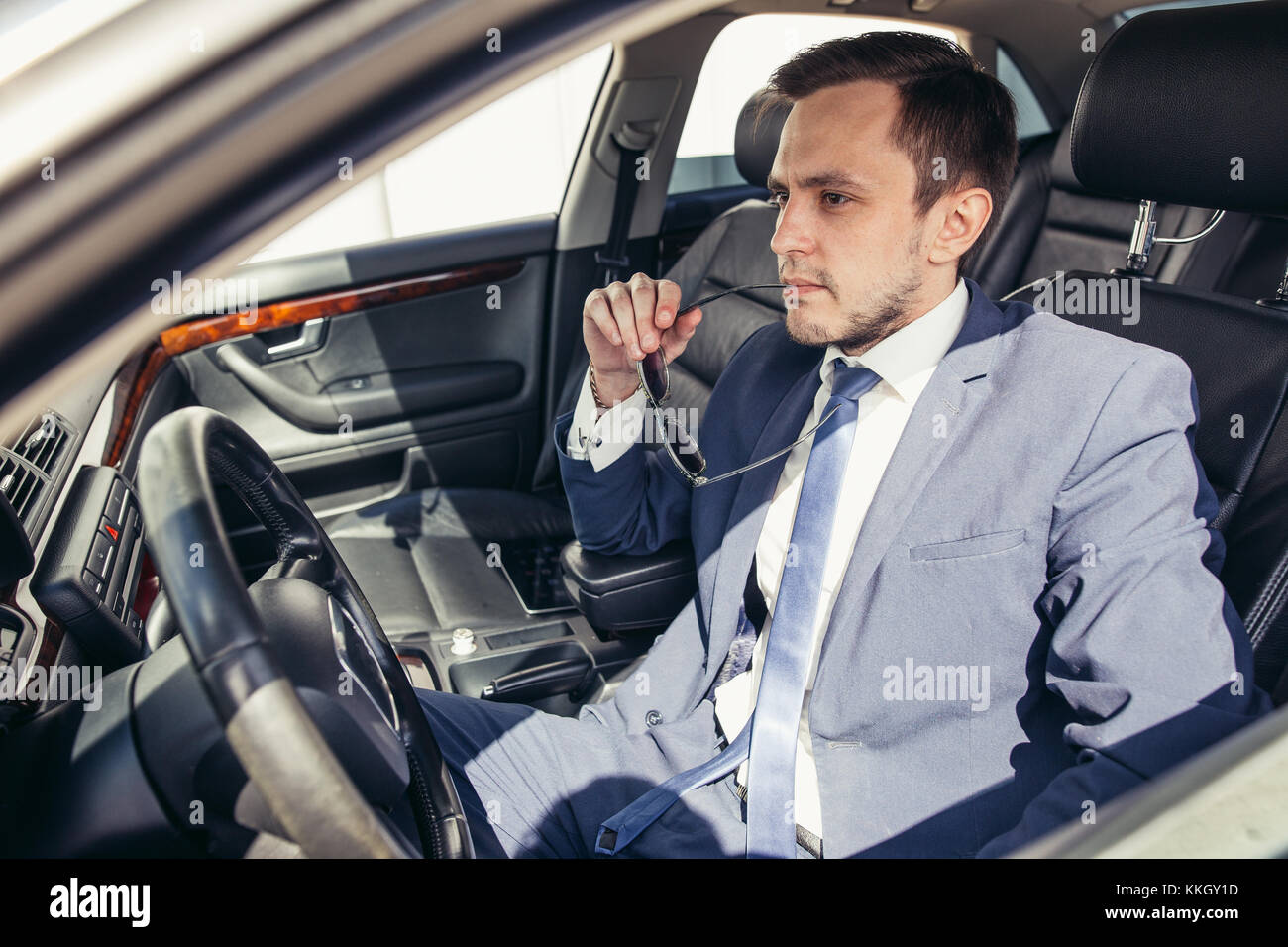 Attractive handsome elegant man in a business suit driving an expensive car - Stock Image
