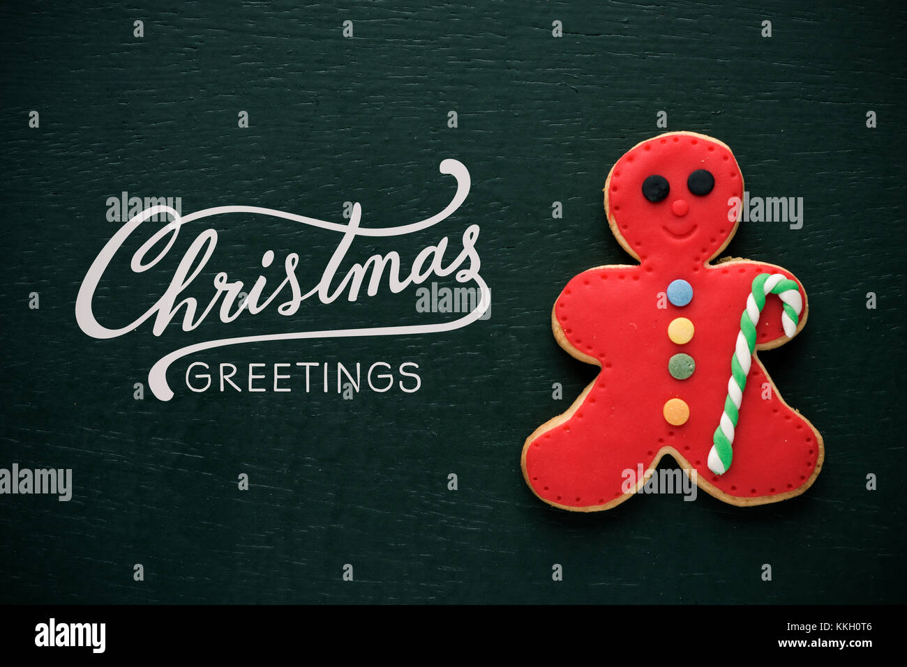 a coloroful cookie in the shape of a gingerbread man and the text christmas greetings on a dark green background - Stock Image