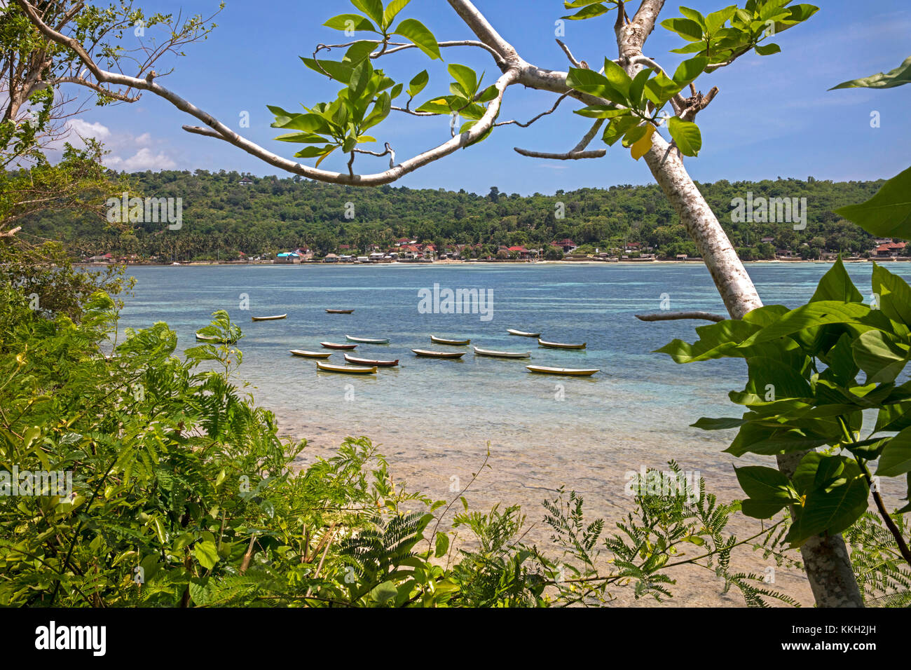 Fishing boats and view over coastal village at the island Nusa Ceningan seen from Nusa Lembongan near Bali in Indonesia - Stock Image