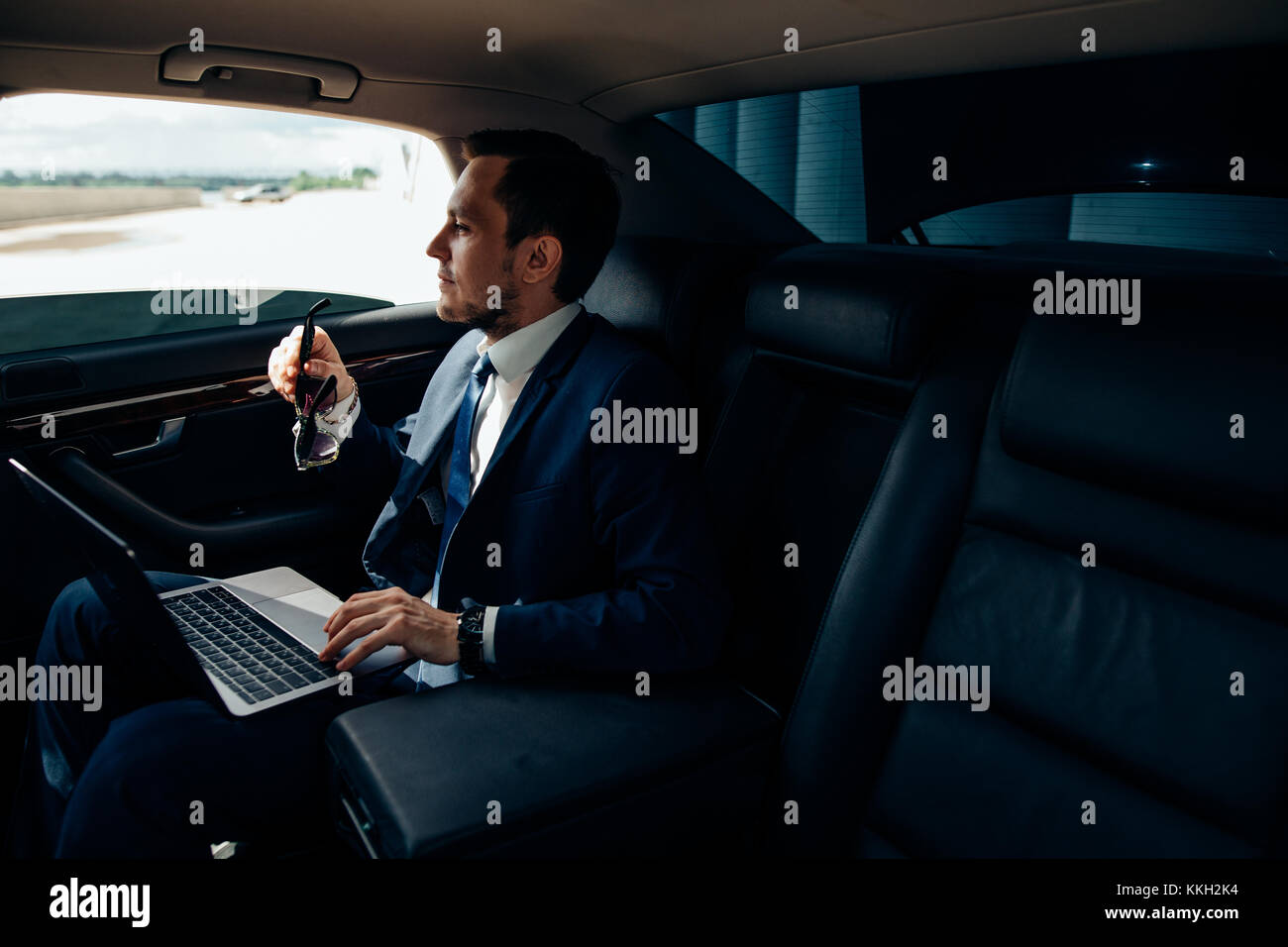 Serious businessman in a car with laptop - Stock Image