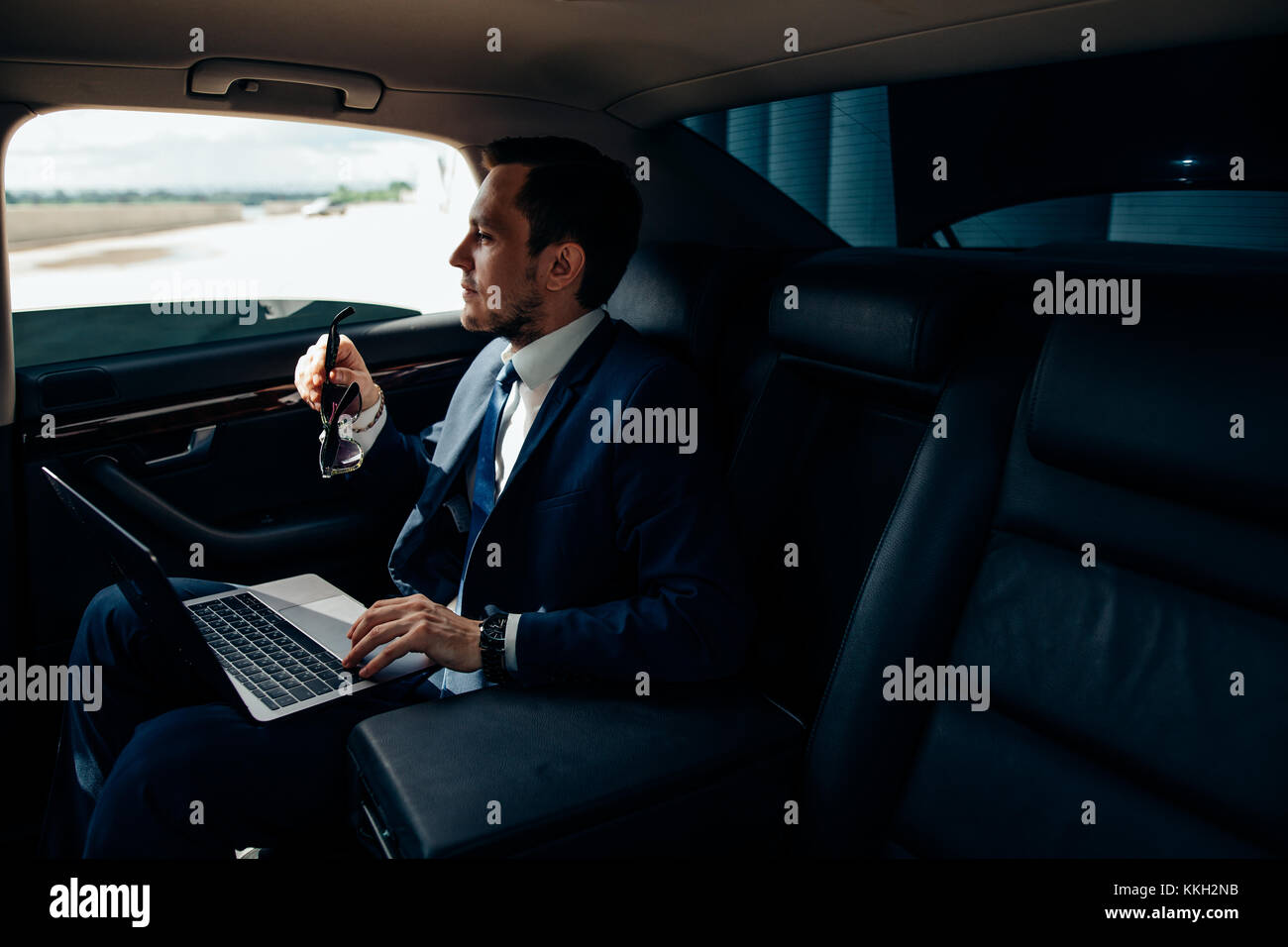 Focusing on work. businessman working on laptop while sitting on back seat car - Stock Image