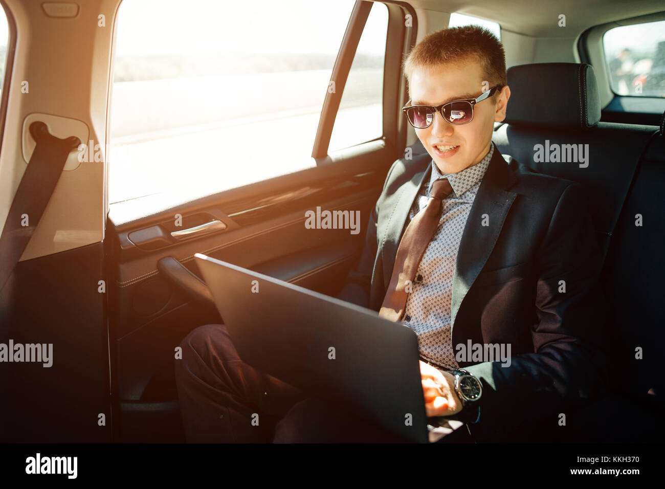 Focusing on work. businessman working on laptop while sitting on back seat car Stock Photo