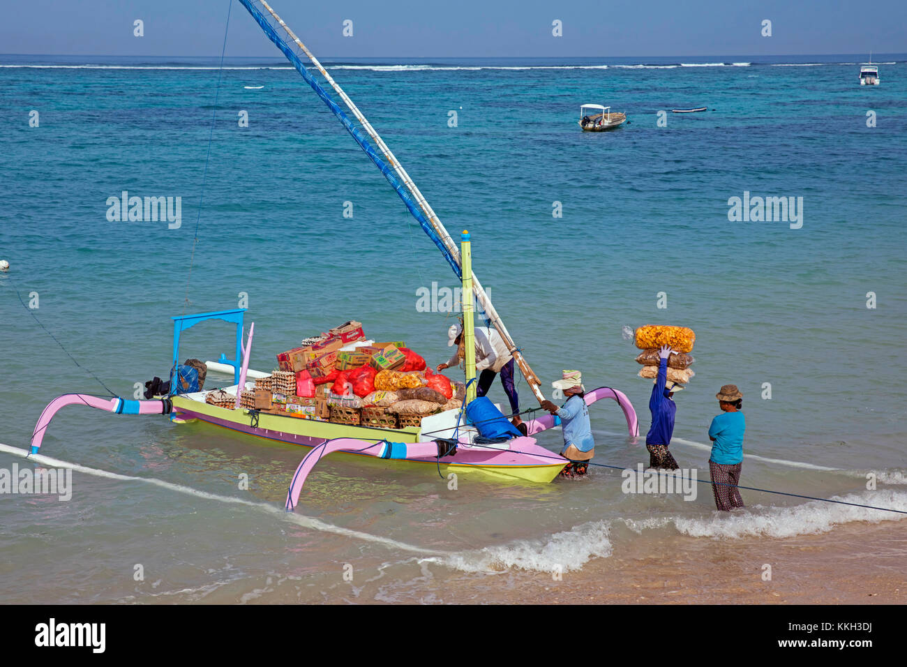 Indonesian women unloading merchandise from traditional outrigger boat to the small island of Nusa Lembongan near - Stock Image