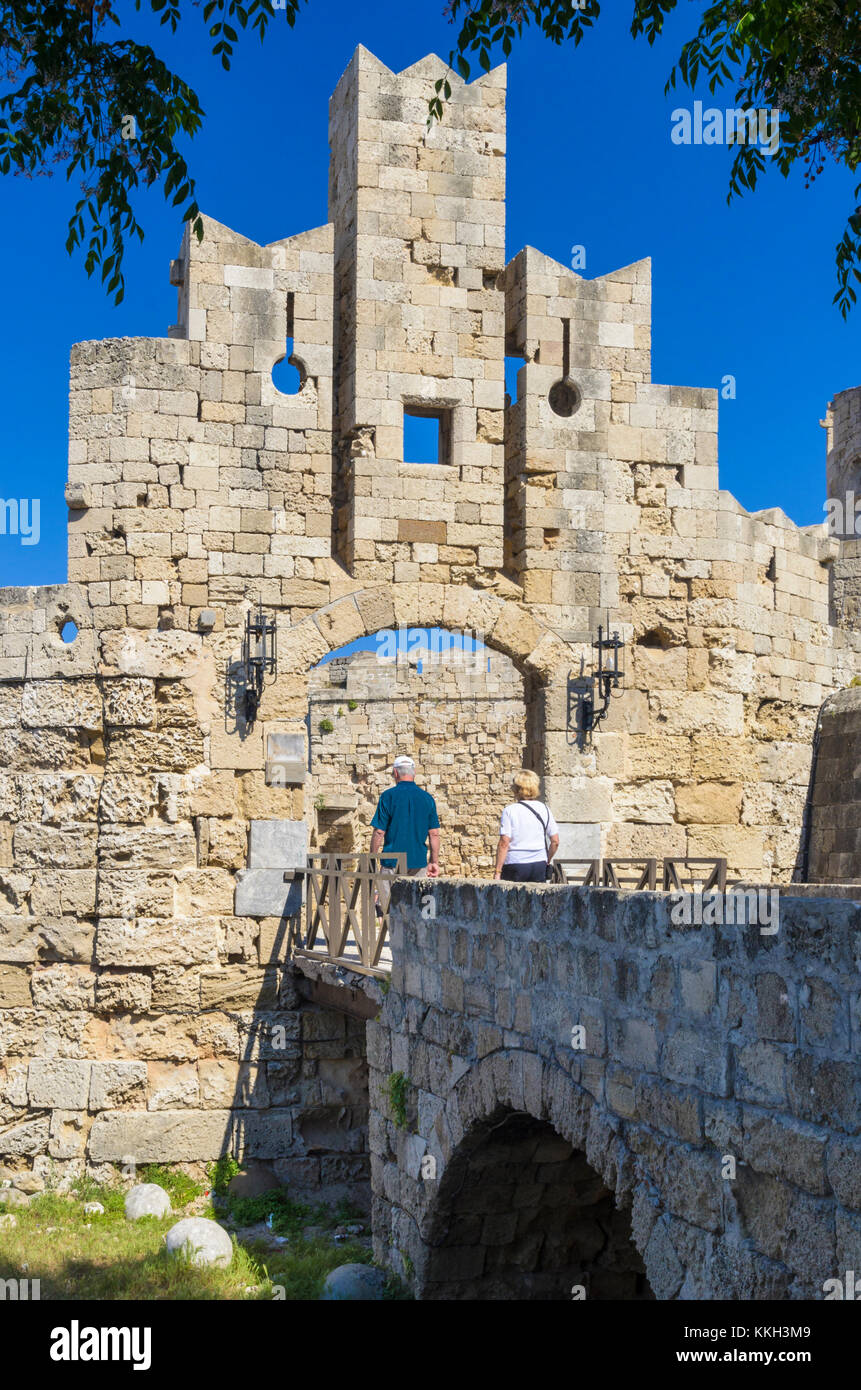 A couple walk through Rhodes castle gate of St Paul, Rhodes Old Town, Rhodes Island, Greece - Stock Image