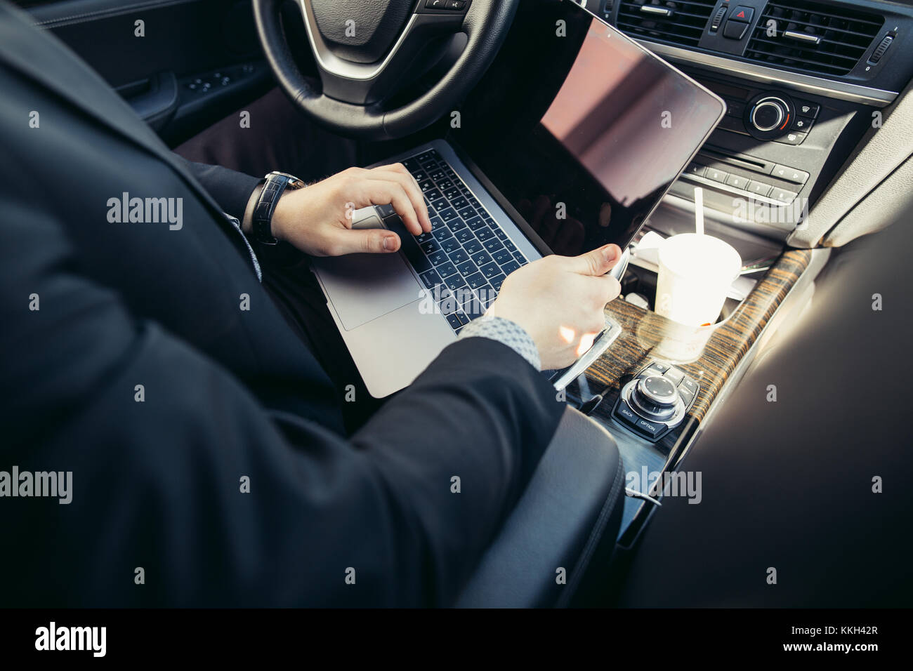 Handsome businessman talking with phone sitting with laptop on backseat of car - Stock Image