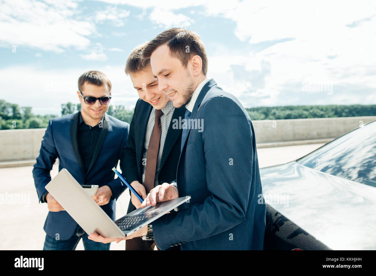 2a9792a905 three Businessman Using Digital Tablet Outside against car - Stock Image