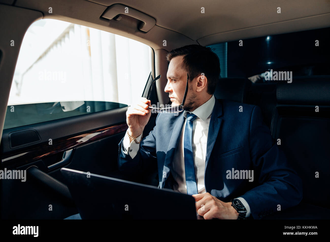 young stylish businessman in sunglasses on backseat of car - Stock Image