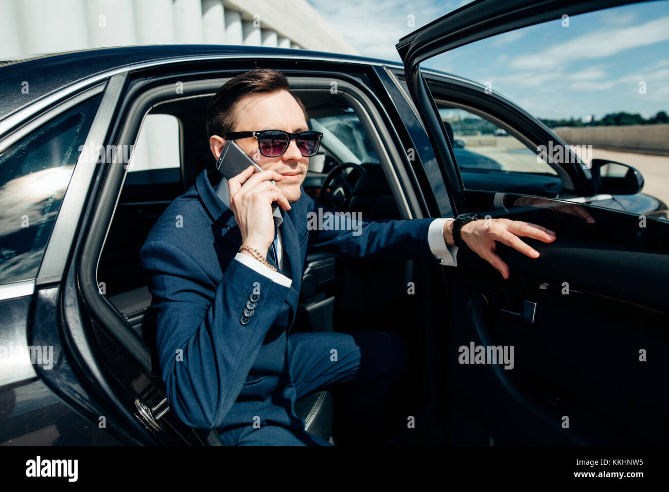 Man in the car reading and phoning - Stock Image