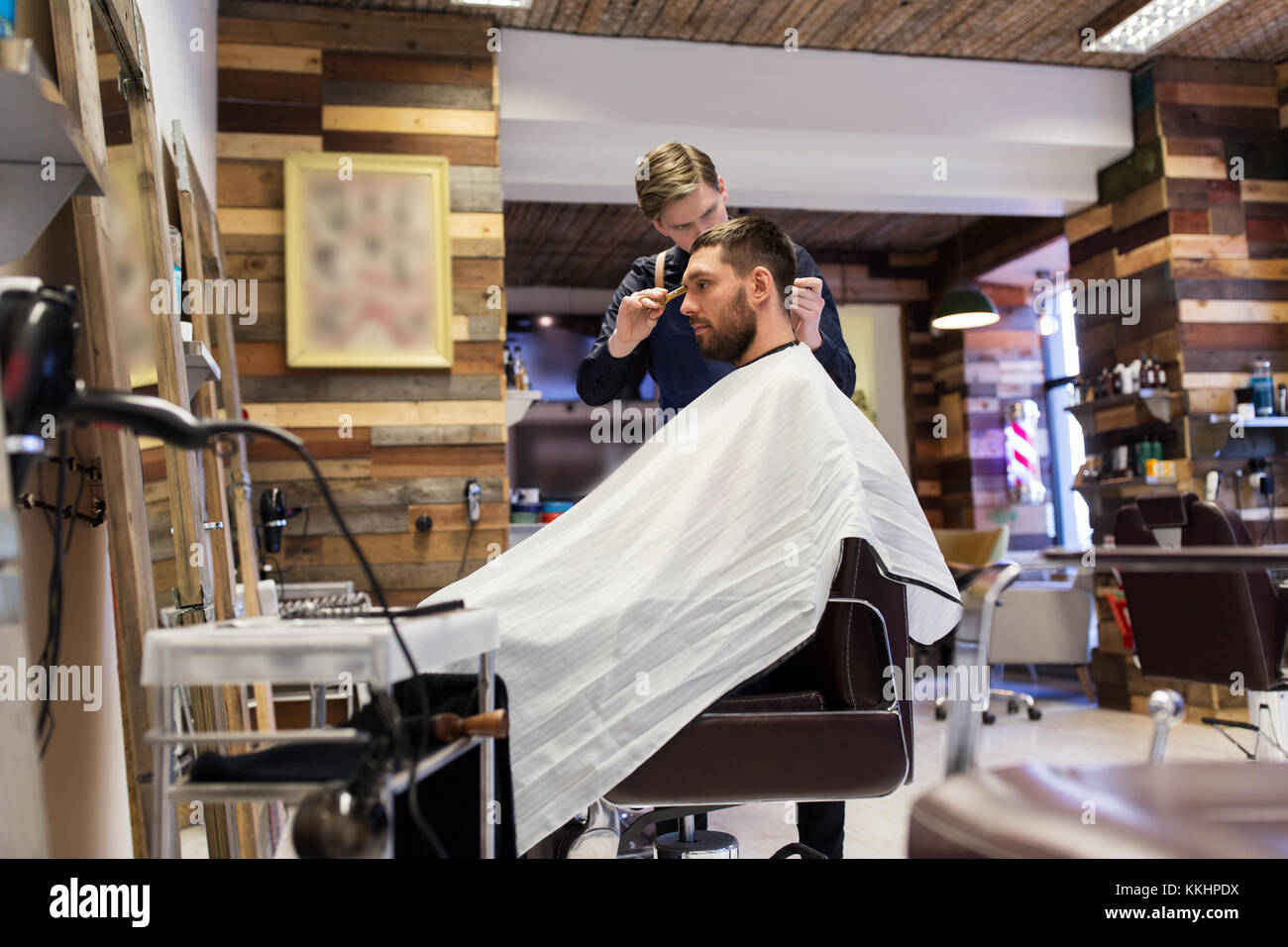 man and barber cutting hair at barbershop - Stock Image
