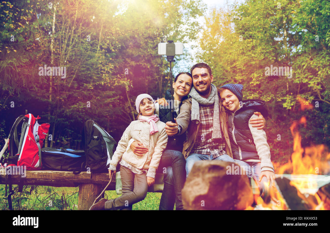 family with smartphone taking selfie near campfire - Stock Image