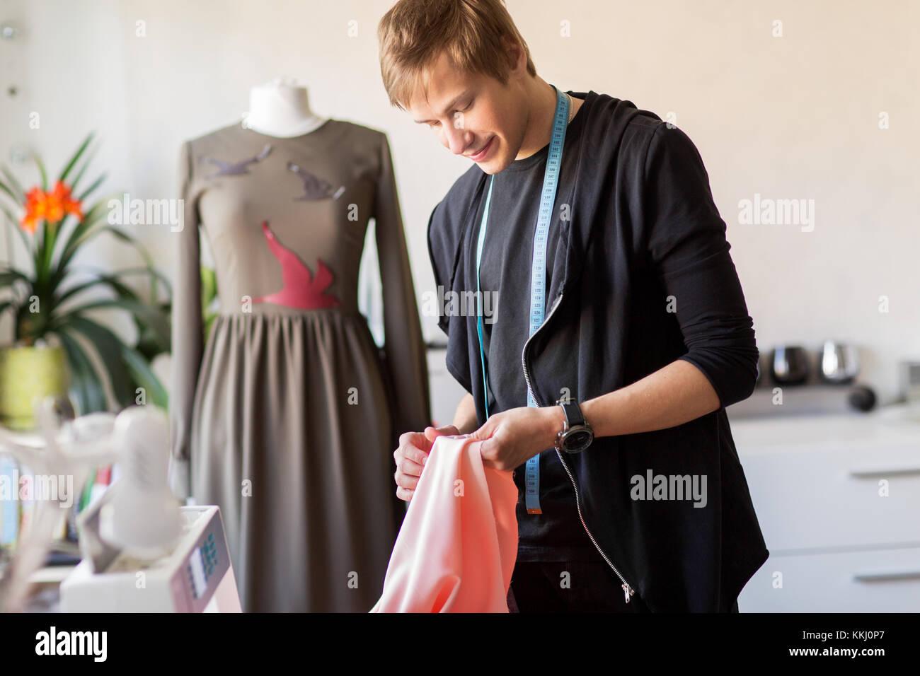 fashion designer with cloth making dress at studio - Stock Image