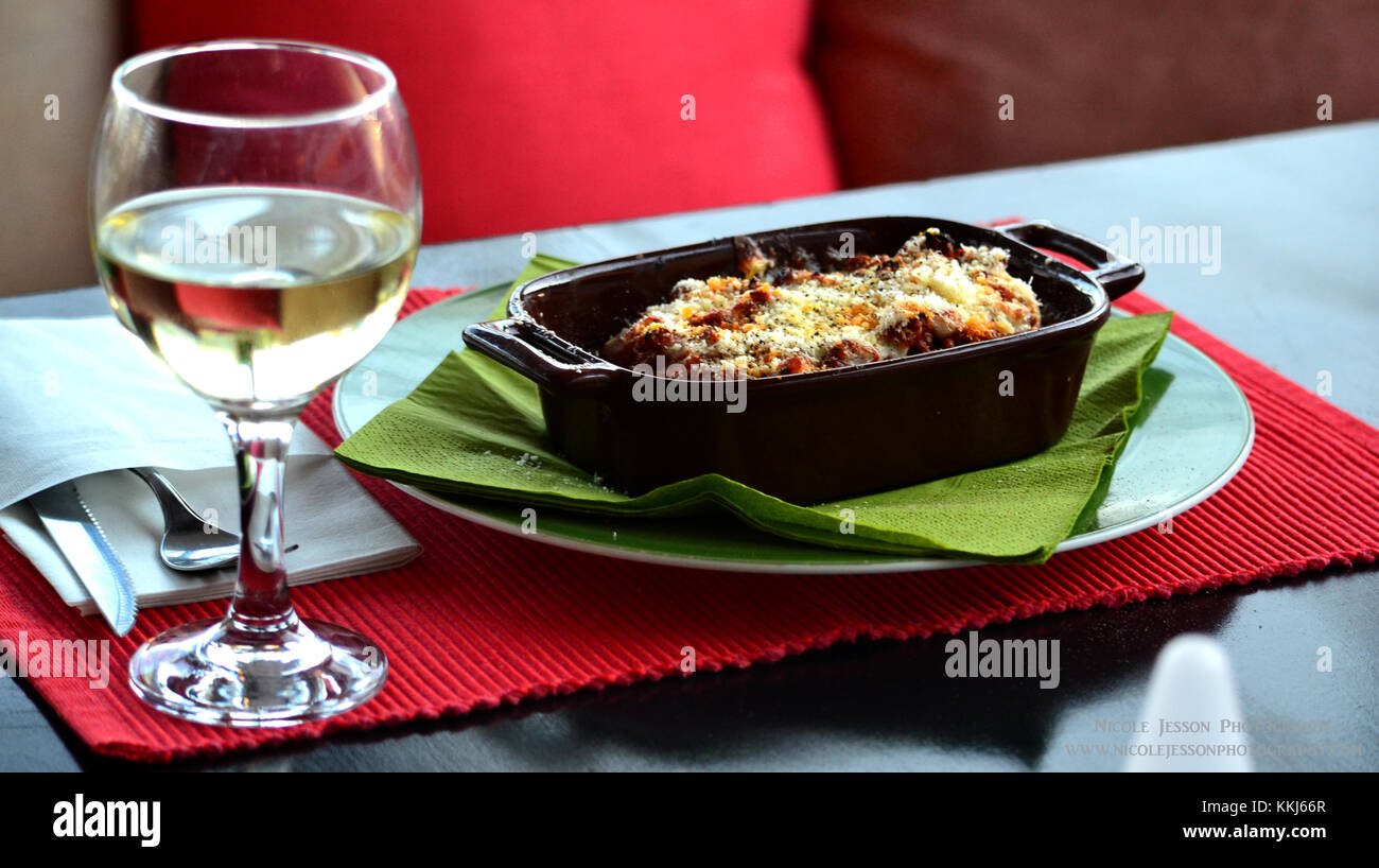 A Greek Lasagna and a wine in the sun - Stock Image