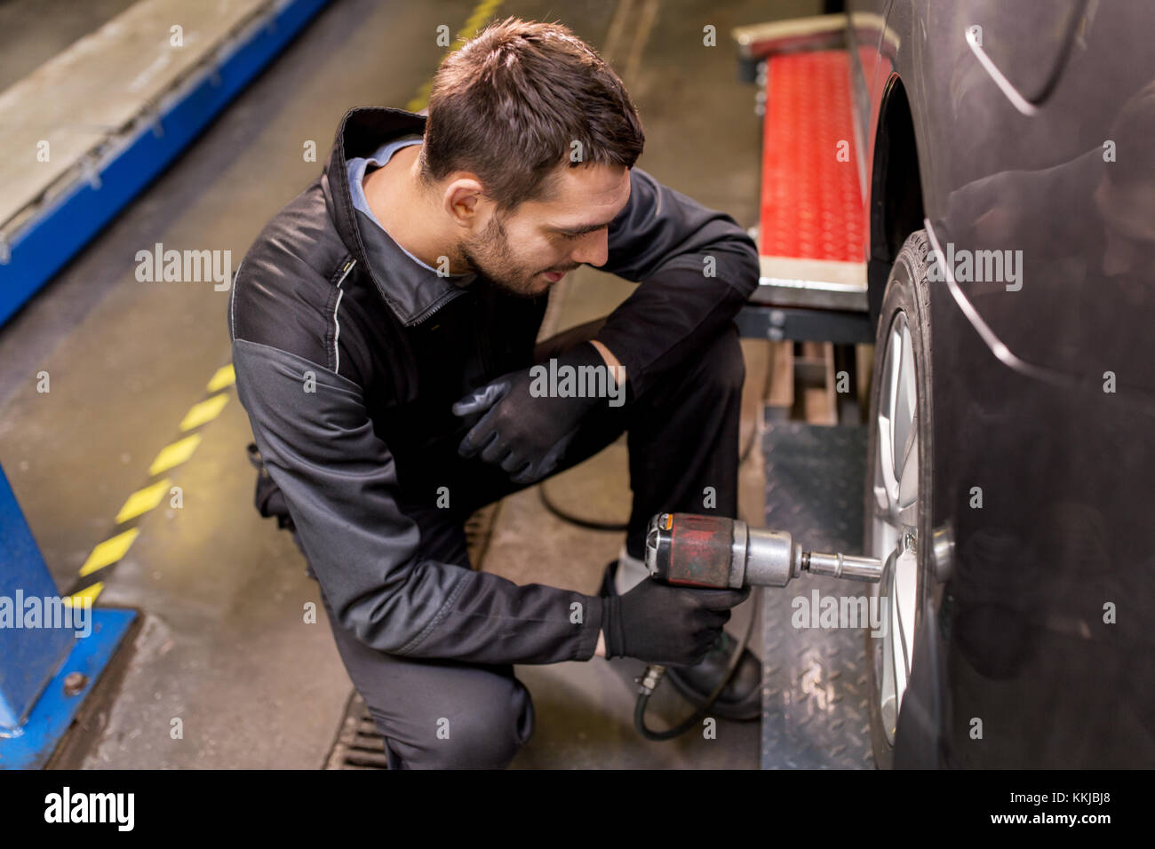 auto mechanic with screwdriver changing car tire - Stock Image