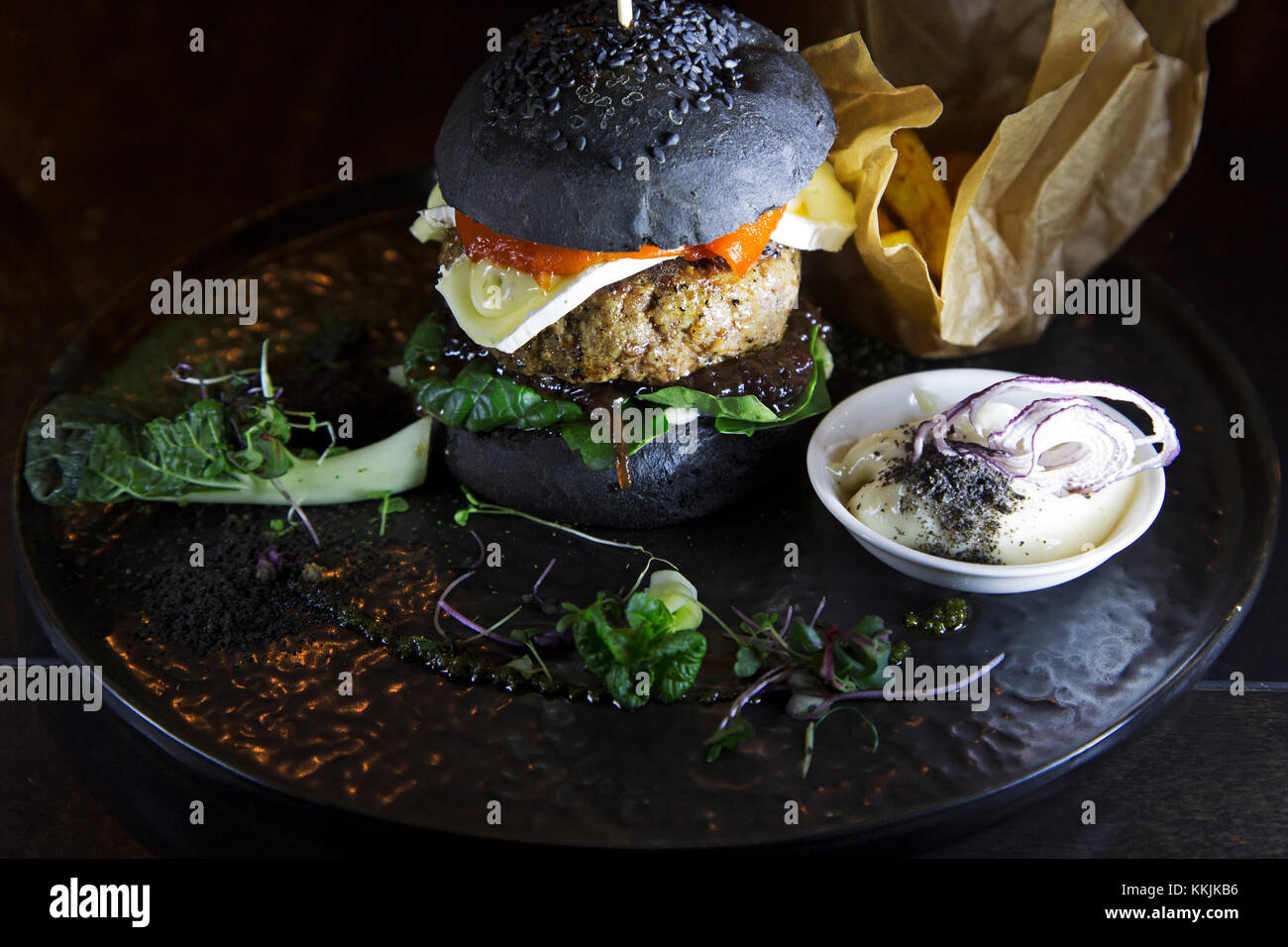 Lamb burger served with in a black bread bun at the Mute restaurant in Riga, Latvia. The burger features a slice - Stock Image
