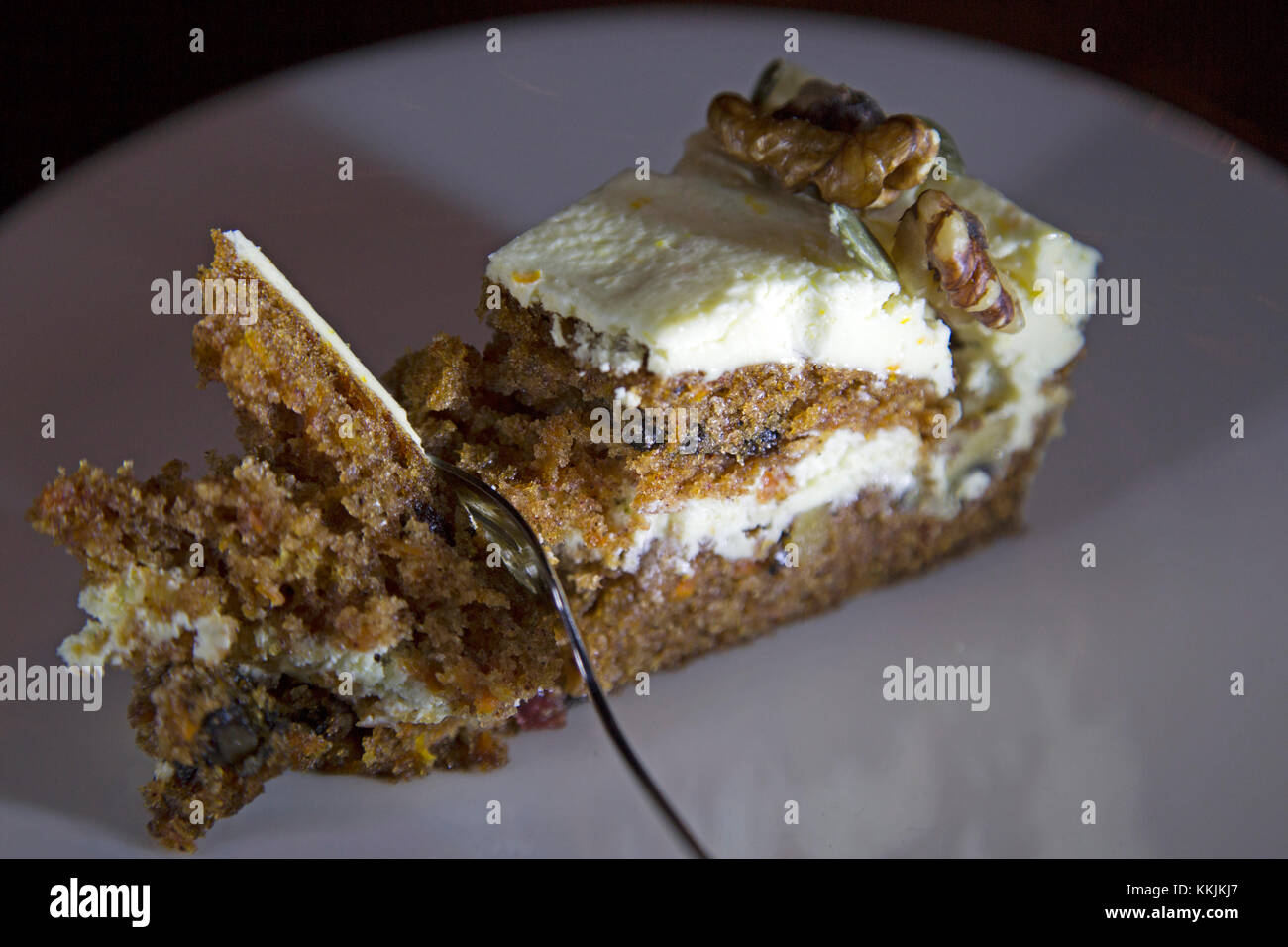 Carrot cake served on a white plate. The cake features fondant and walnuts. - Stock Image