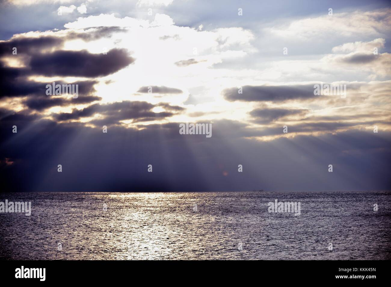 Light streams from the heavens as the sun breaks above storm clouds above Lake Michigan off shore of Montrose Harbor - Stock Image