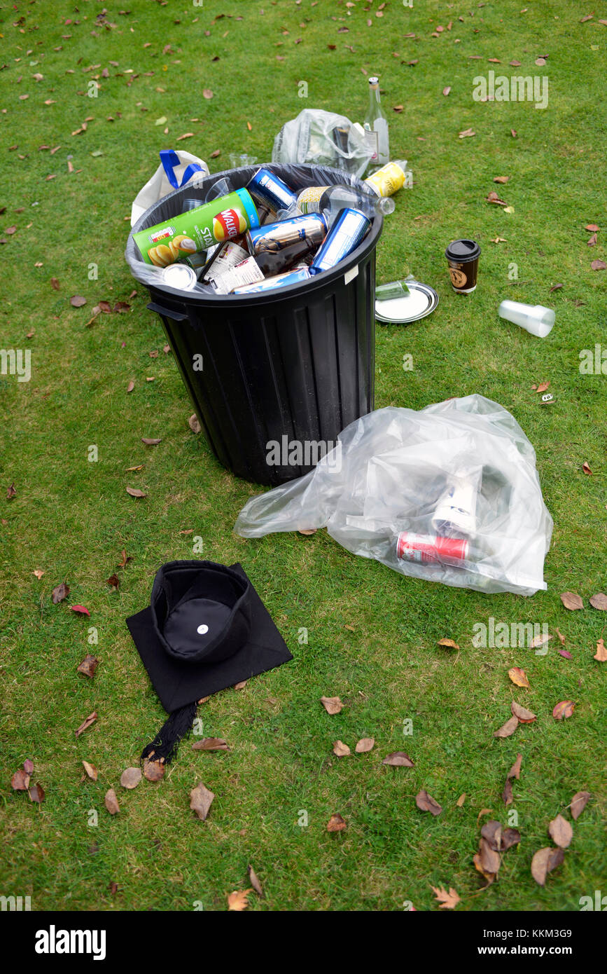 A discarded mortarboard lies next to rubbish in an Oxford college garden after an end-of-year party to celebrate - Stock Image