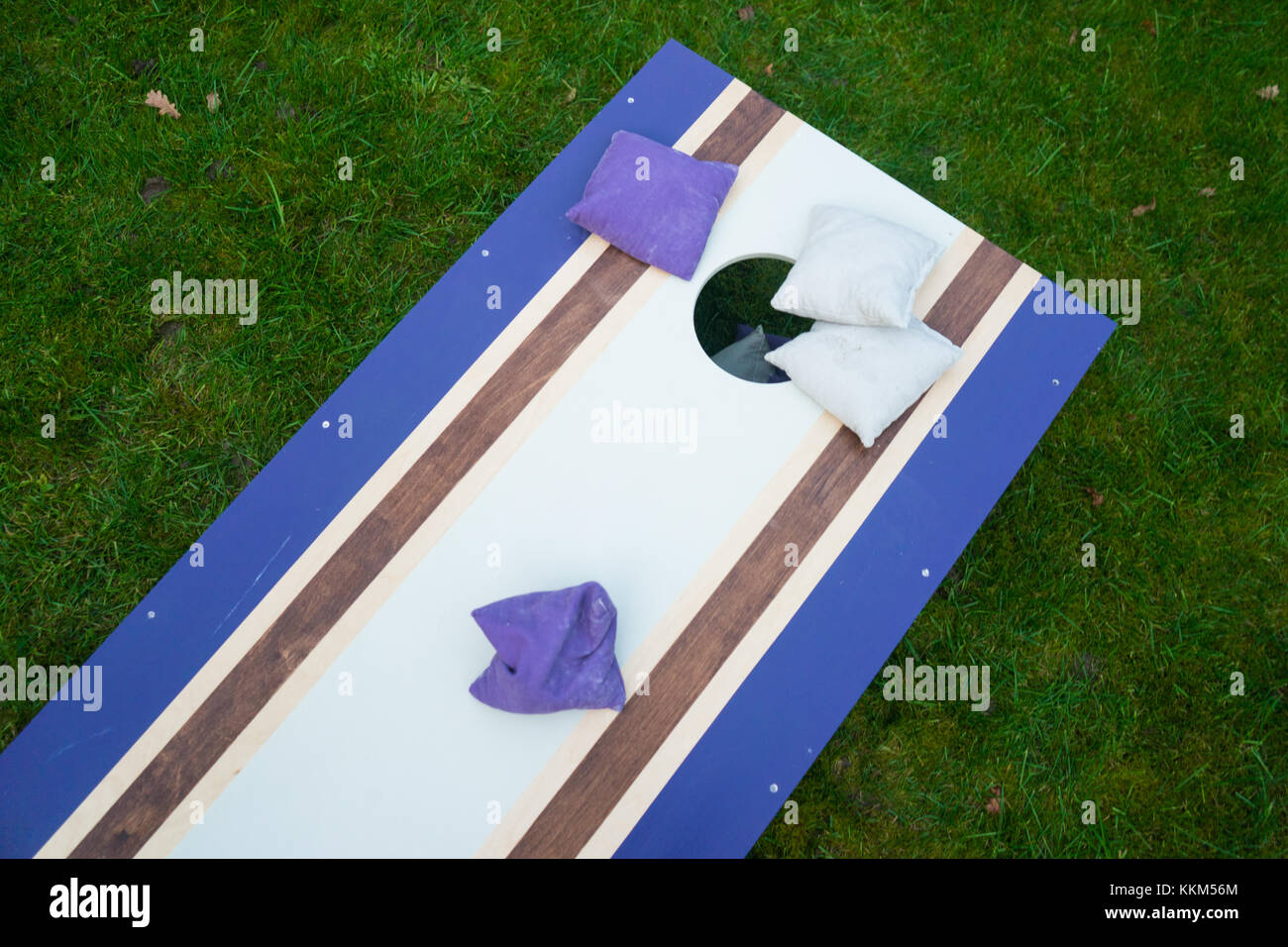 Cornhole beanbag toss wood game board outside on grass - Stock Image