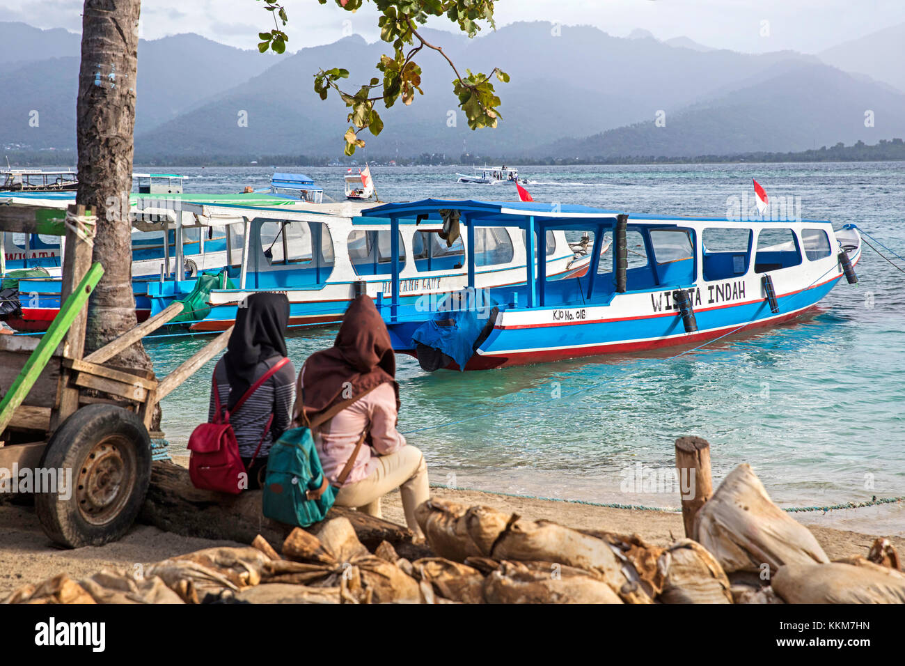 Two Indonesian women waiting for the ferry to the island Lombok at Gili Air, one of the Gili Islands in Indonesia - Stock Image