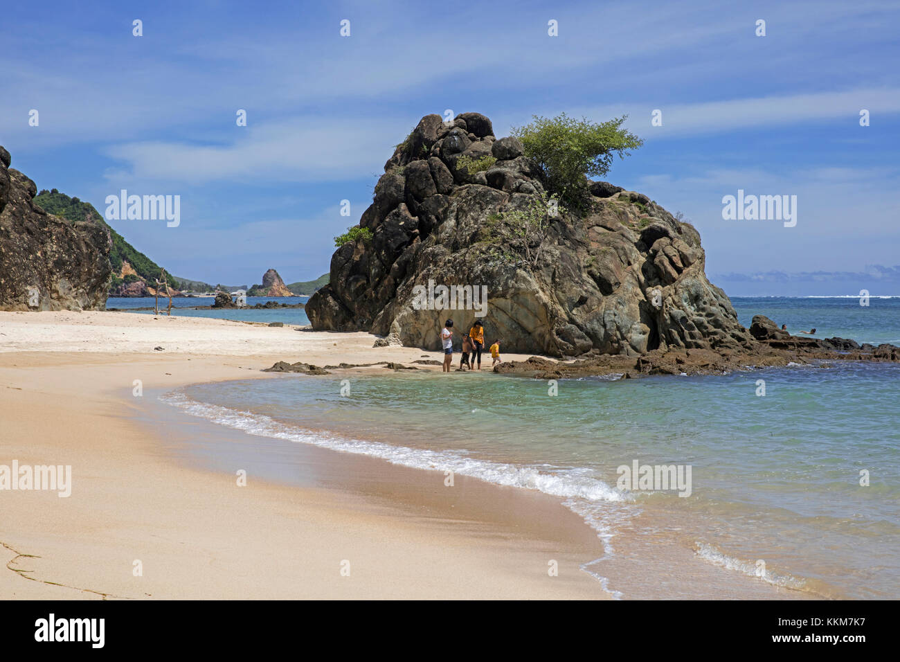 Indonesian children playing on white sandy beach at Kuta on the island Lombok, Lesser Sunda Islands, Indonesia - Stock Image