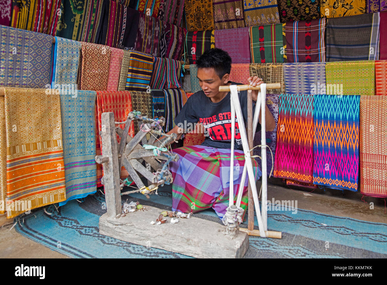 Indonesian weaver weaving traditional songket fabrics on primitive wooden loom in the Sasak village Sade on the - Stock Image