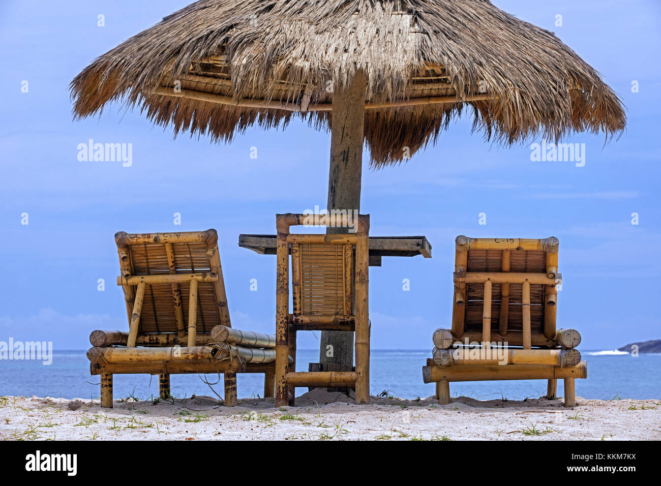 Relaxing bamboo deck chairs with parasol on white sandy beach looking towards ocean at Pantai Tanjung Aan on the - Stock Image