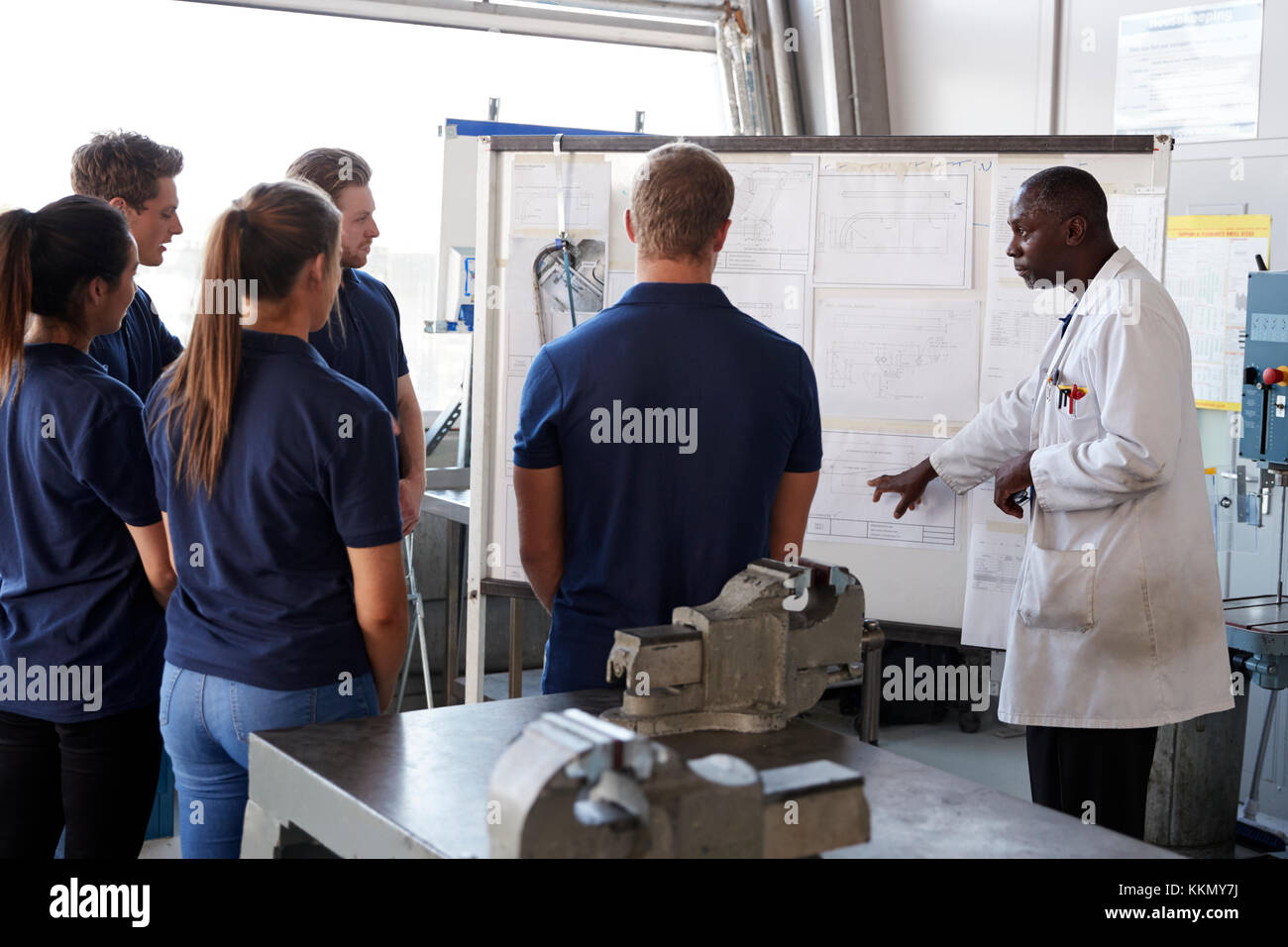 Engineer instructing apprentices at a whiteboard, close up - Stock Image