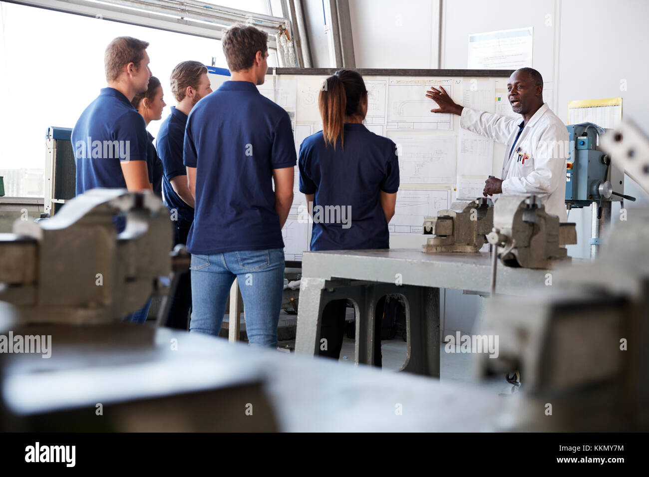 Engineering apprentices watching presentation at whiteboard - Stock Image