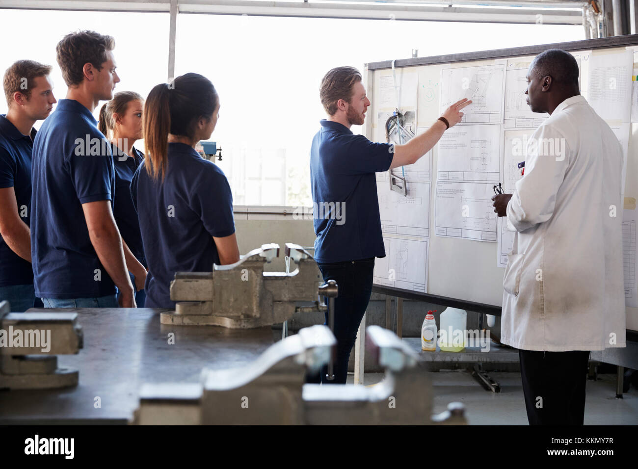 Engineering apprentice presenting to group at whiteboard - Stock Image