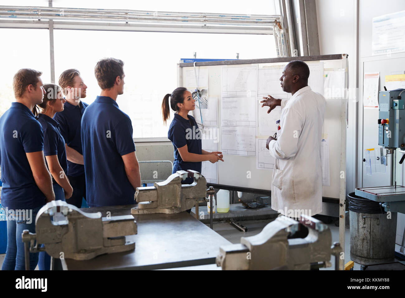 Engineer and female apprentice presenting at whiteboard - Stock Image