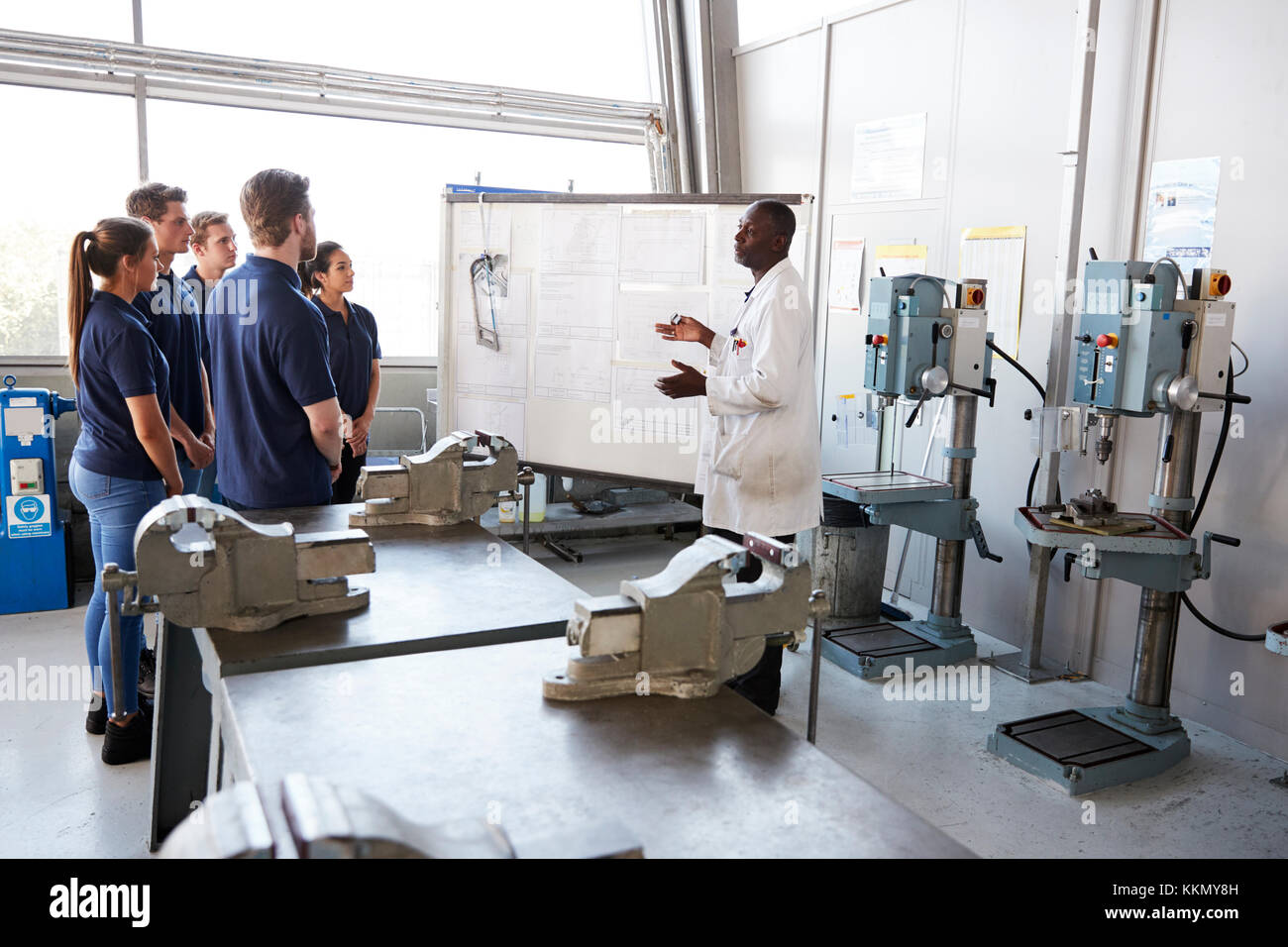 Engineer instructing apprentices at a whiteboard, side view - Stock Image