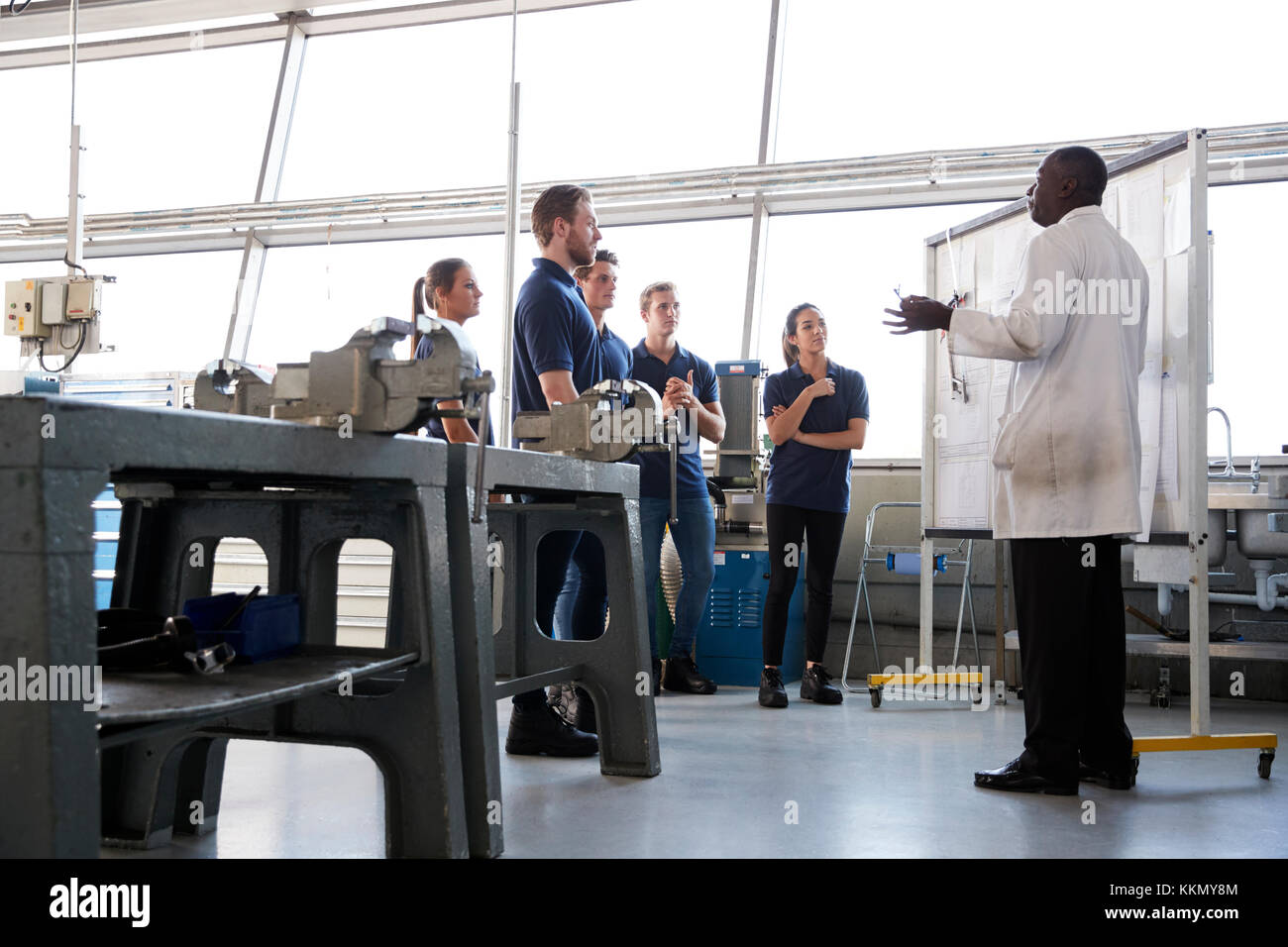 Engineering apprentices stand at a training presentation, low angle - Stock Image
