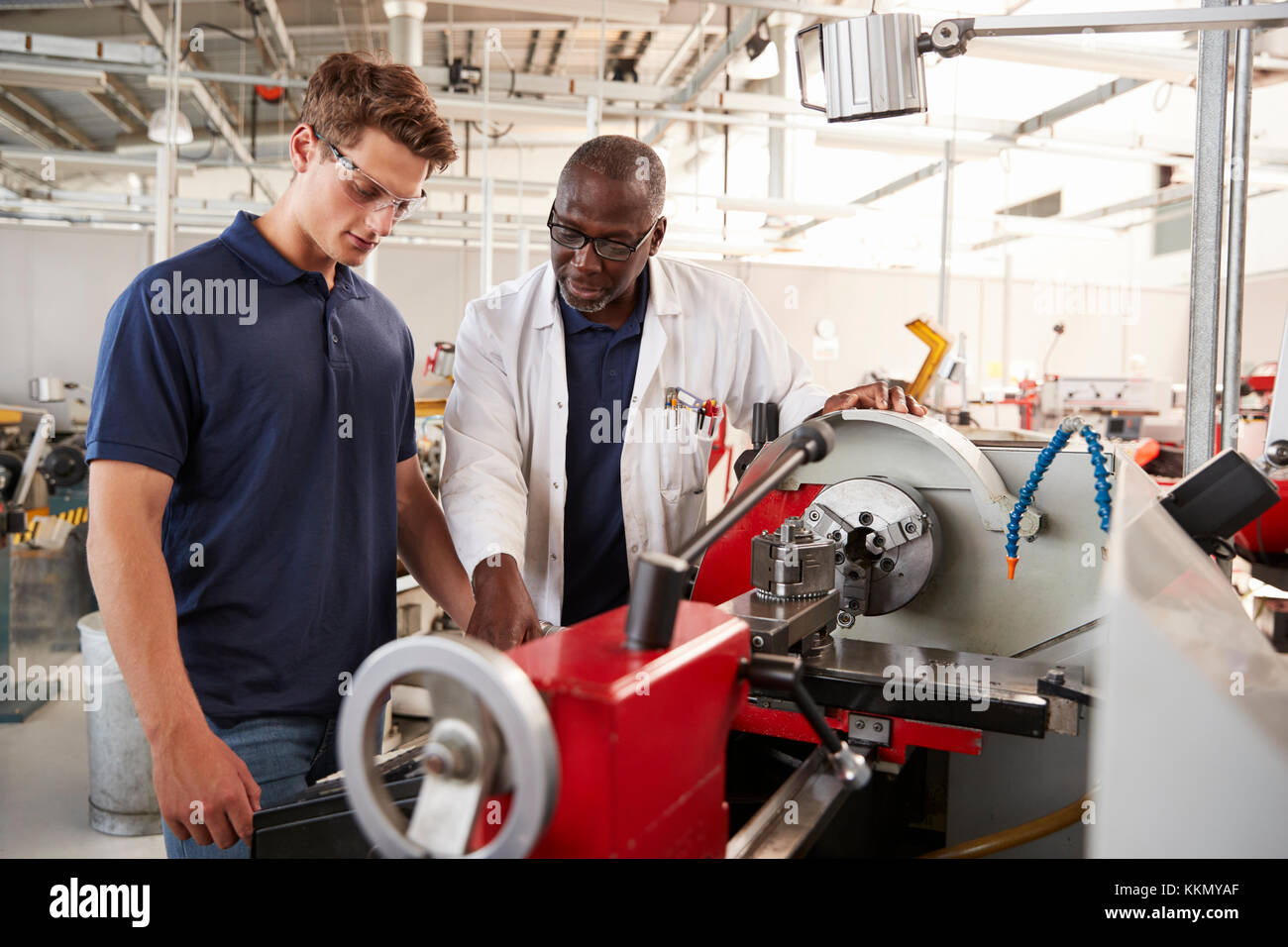 Engineer showing male apprentice how to operate machinery, close up - Stock Image