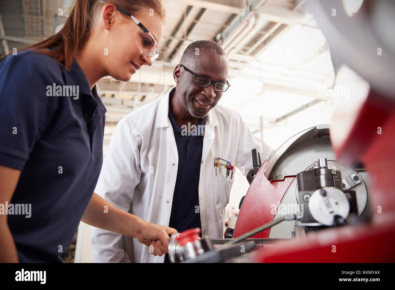 Engineer showing female apprentice how to operate machinery, close up - Stock Image
