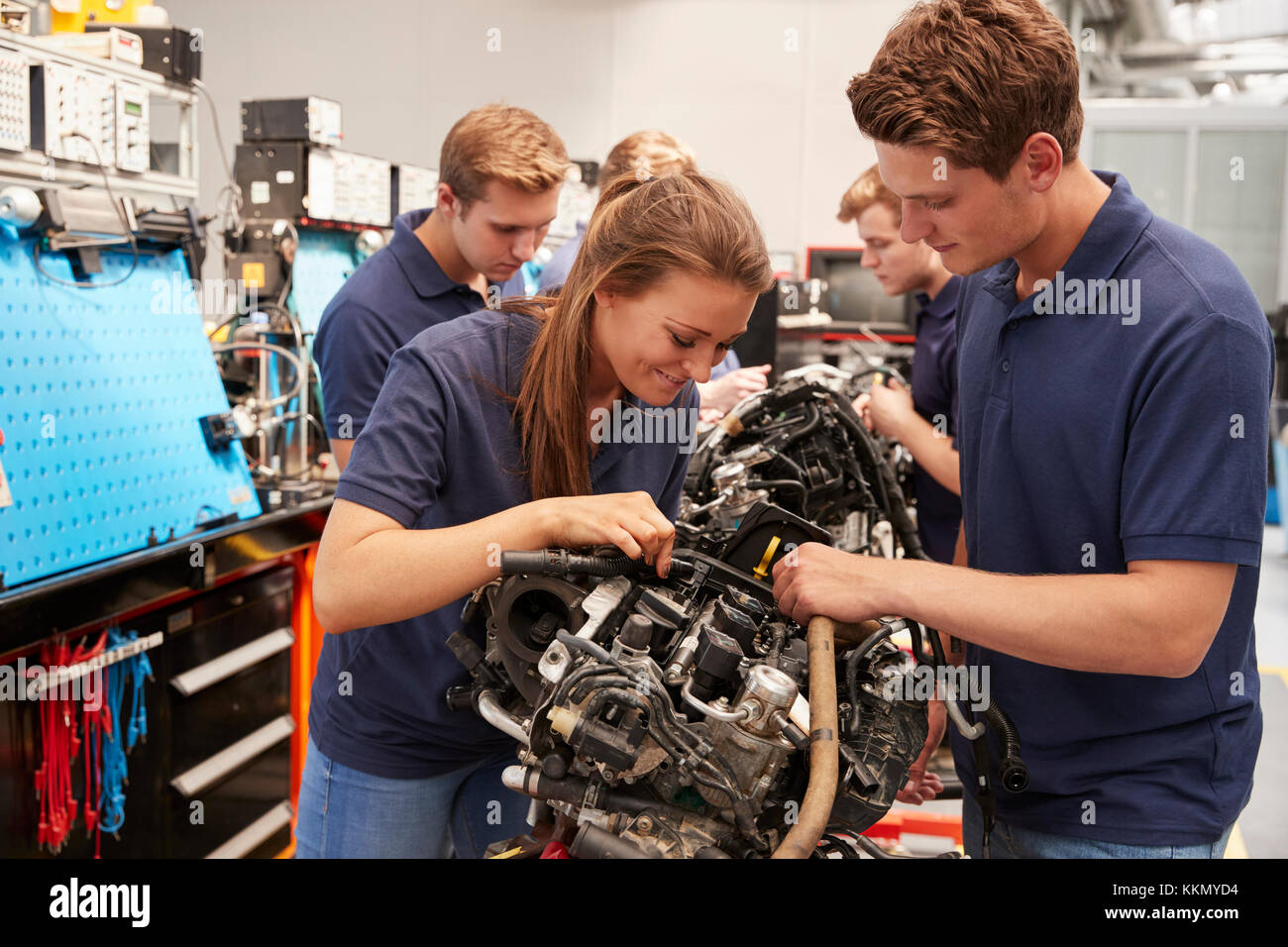 Apprentice car mechanics working on an engine - Stock Image