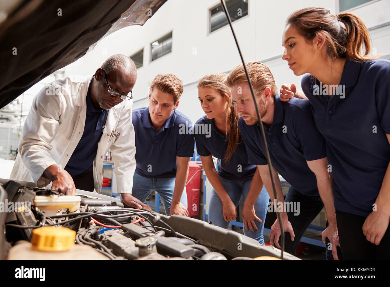 Mechanic instructing trainees around a car engine, low angle - Stock Image