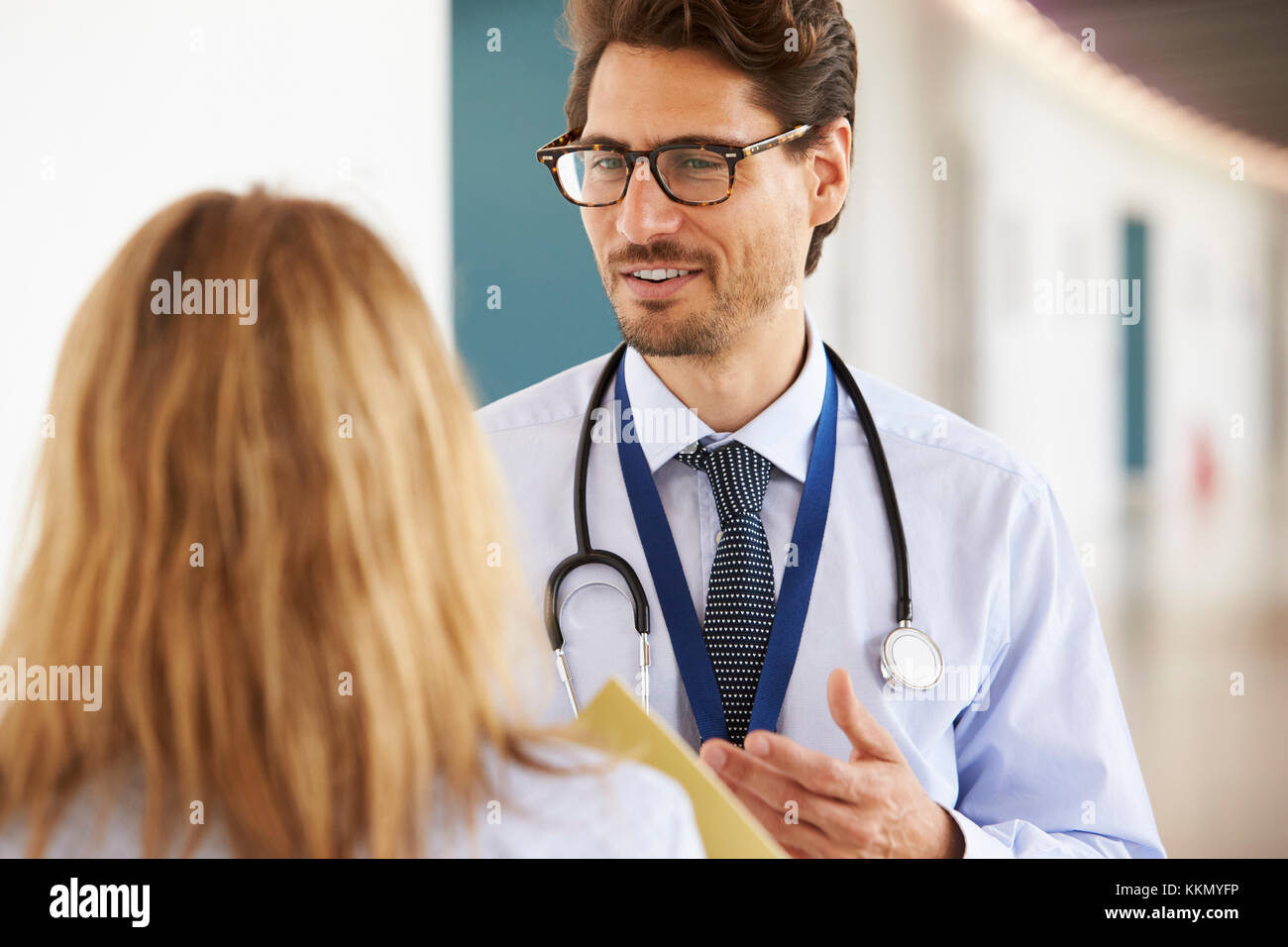 Young male and female doctors talking, close up - Stock Image