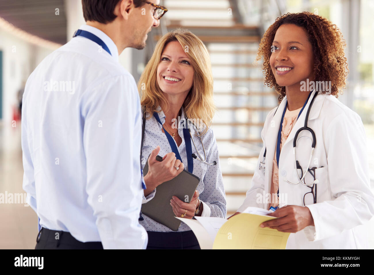 Three young male and female doctors in consultation - Stock Image