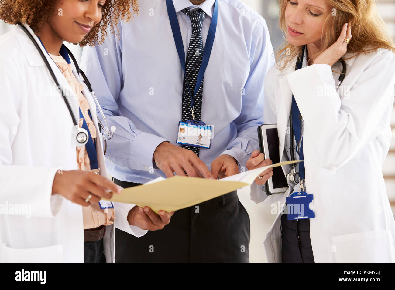 Three young male and female doctors consulting, mid section - Stock Image