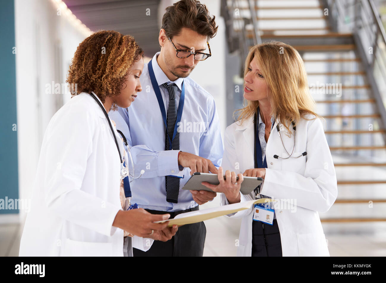Three young male and female doctors consulting - Stock Image