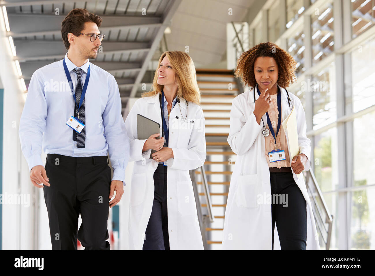 Three young male and female doctors walking in hospital - Stock Image