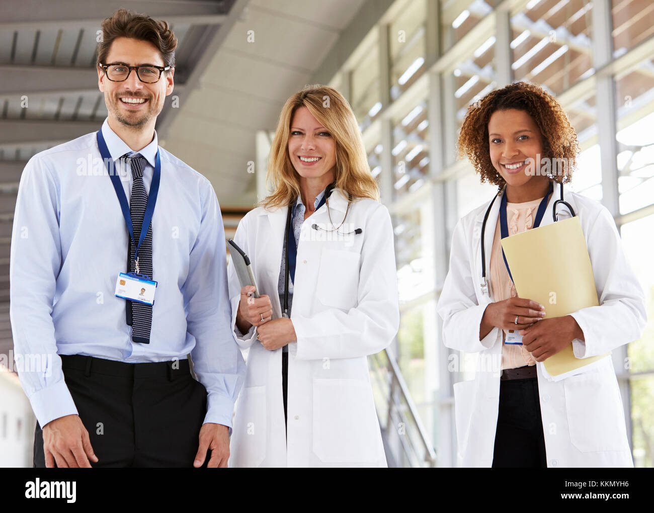 Portrait of three male and female doctors, looking to camera - Stock Image