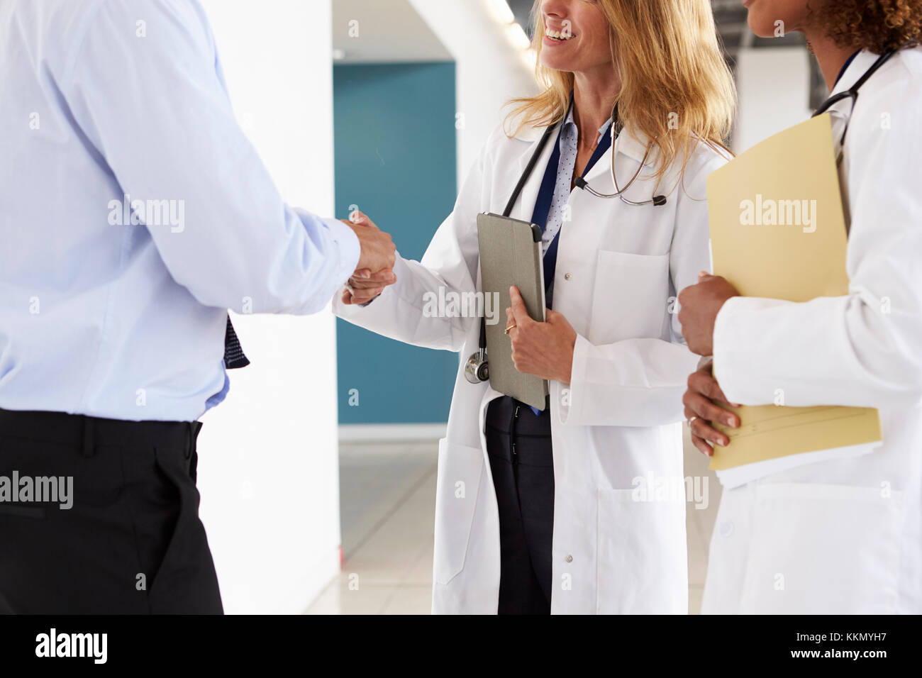Three male and female doctors shaking hands, mid section - Stock Image