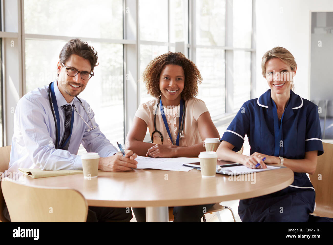 Senior healthcare workers in a meeting looking to camera - Stock Image