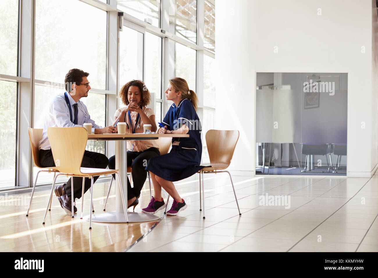 Three senior healthcare workers in a meeting, low angle - Stock Image